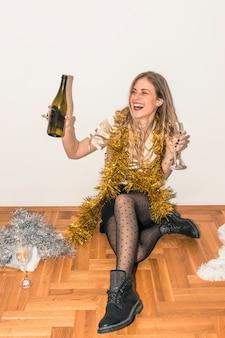 Mulher feliz, sentar chão, com, garrafa champanha