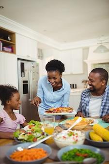 Mulher feliz servindo comida para a família