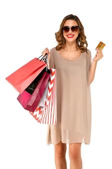 Mulher feliz shopper no vestido de verão com sacos de compras, segurando o cartão de crédito