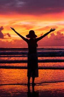 Mulher feliz silhueta no lindo céu pôr do sol e tropical praia e mar
