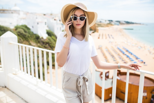 Mulher feliz smartphone falando ao telefone enquanto relaxa ao ar livre nas férias na europa