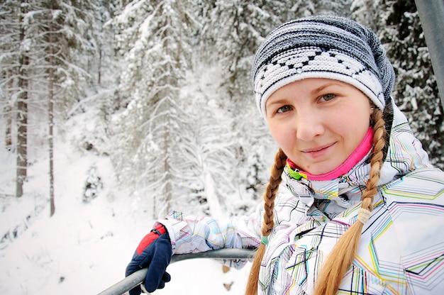 Mulher feliz sobe no elevador nas montanhas dos cárpatos. fechar-se. natureza do inverno. queda de neve forte. duas tranças na cabeça.