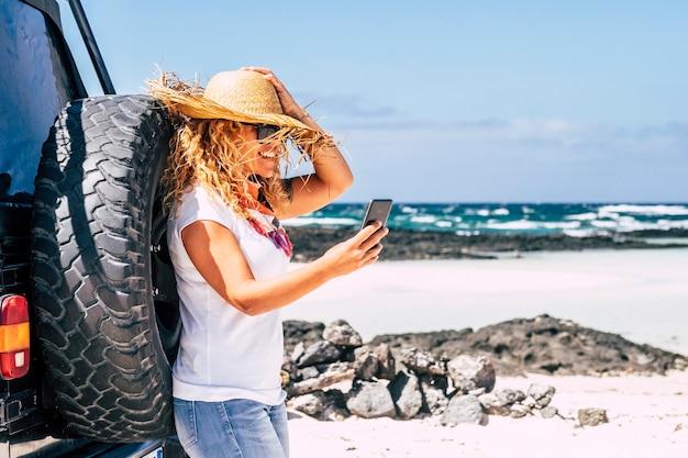Mulher feliz sorri e usa conexão de roaming de telefone na praia em viagem de carro.