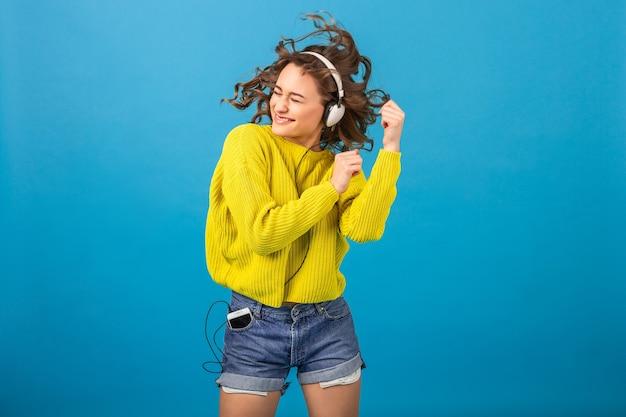 Mulher feliz sorridente atraente dançando ouvindo música em fones de ouvido em roupa elegante hippie isolada no fundo azul do estúdio, vestindo shorts e suéter amarelo