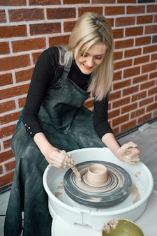Mulher feliz sorridente fazendo cerâmica cerâmica na roda.