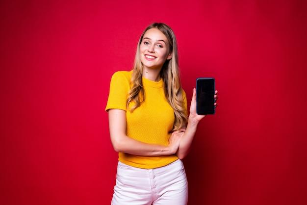 Mulher feliz sorrindo e apontando o dedo de lado na tela preta do celular isolado na parede vermelha