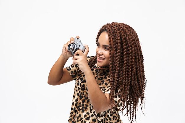 Mulher feliz sorrindo e fotografando na câmera retro, isolado contra uma parede branca