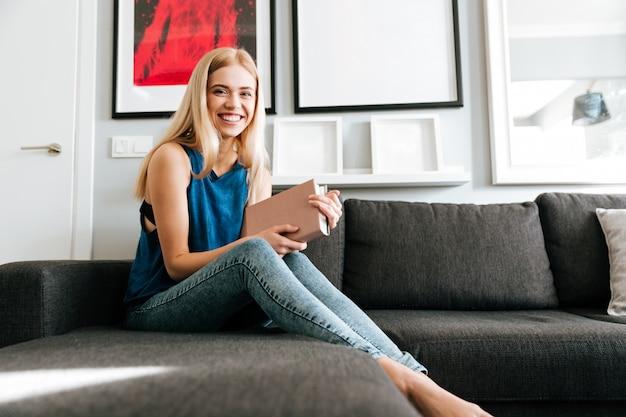 Mulher feliz, sorrindo e lendo o livro no sofá em casa