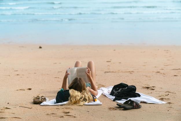 Mulher feliz sorrindo e ler livros na praia em uma bela