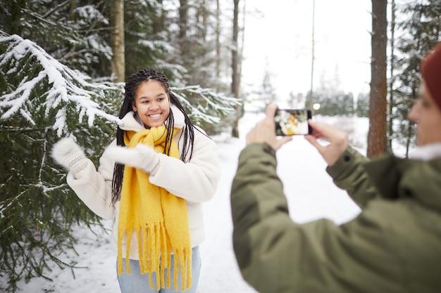 Mulher feliz sorrindo e posando para a câmera enquanto um homem tirando uma foto no celular na floresta