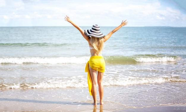 Mulher feliz sorrindo e se divertindo na praia. retrato do verão da menina bonita na praia com um lenço e um chapéu amarelos.
