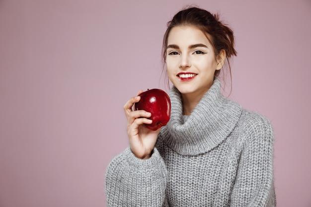 Mulher feliz, sorrindo, segurando a maçã vermelha na rosa