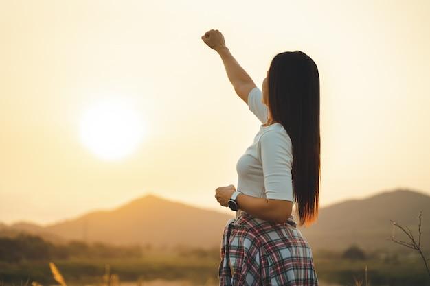 Mulher feliz sucesso levantando as mãos na montanha