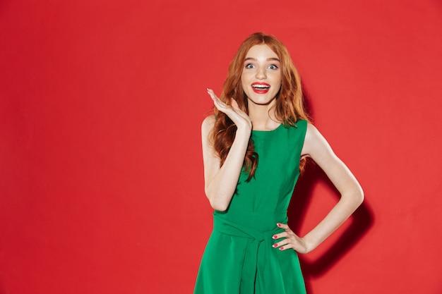 Mulher feliz surpresa com vestido verde com o braço no quadril