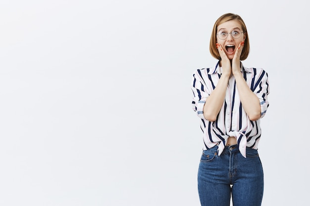 Mulher feliz surpresa e animada de óculos parecendo divertida, ouve boas notícias, regozijando