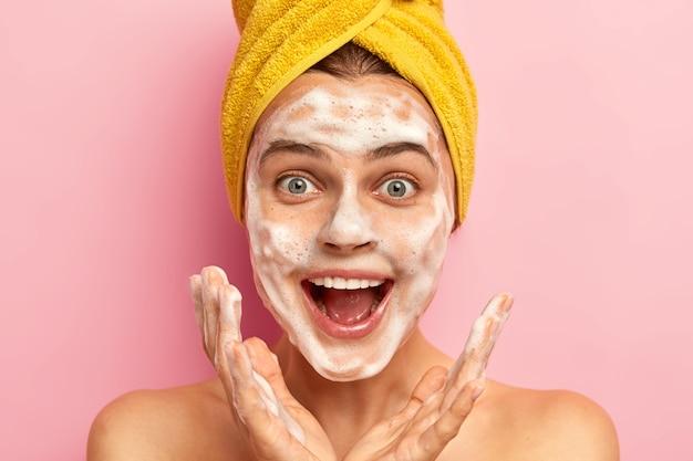 Mulher feliz surpresa espalha as palmas das mãos perto do rosto, tem expressão alegre, se olha no espelho do banheiro, lava o rosto com sabonete,