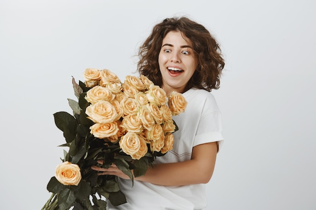 Mulher feliz surpresa recebe lindo buquê de flores, entrega na floricultura