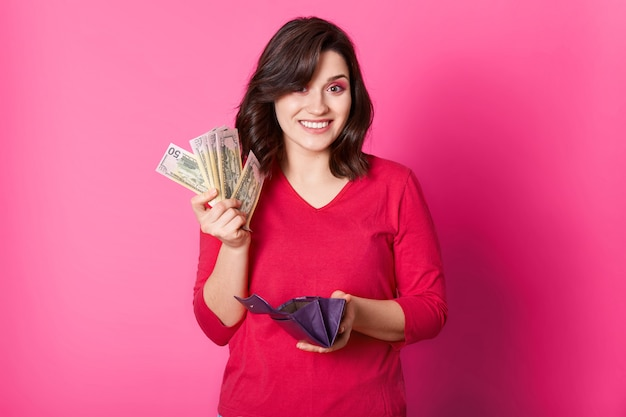 Mulher feliz tem carteira e dinheiro nas mãos, pensa em como gastar seu salário. menina morena estar feliz em ir às compras