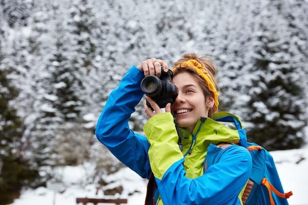Mulher feliz tira foto de montanhas cobertas de neve, passa as férias de inverno na natureza e usa jaqueta brilhante