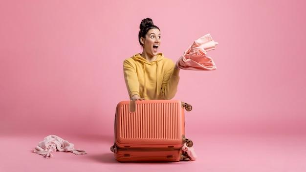 Mulher feliz tirando as roupas da bagagem