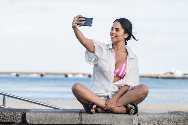Mulher feliz tirando autorretrato à beira-mar