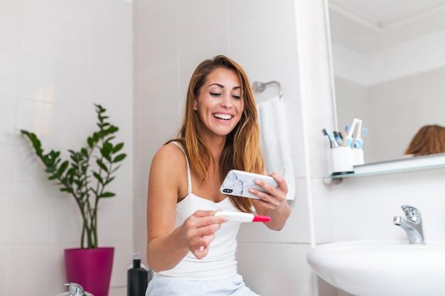 Mulher feliz tirando foto do teste de gravidez com telefone celular e postar imagens nas mídias sociais.