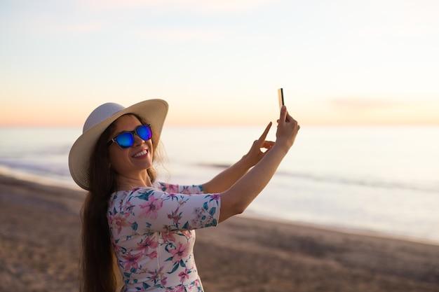Mulher feliz tirando fotos para o mar com a câmera do smartphone no verão viagem de férias para a costa
