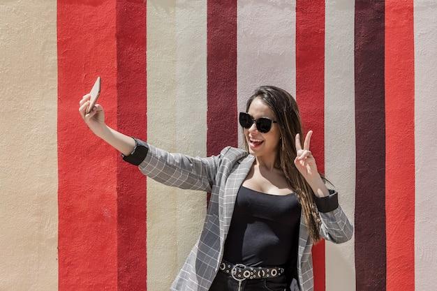 Mulher feliz tirando selfie na cidade