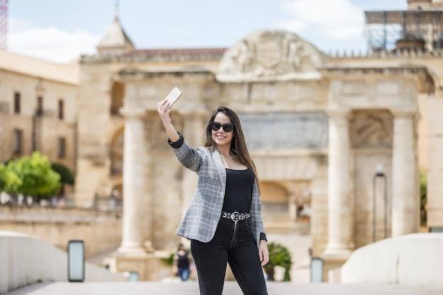 Mulher feliz tirando uma selfie contra prédio histórico