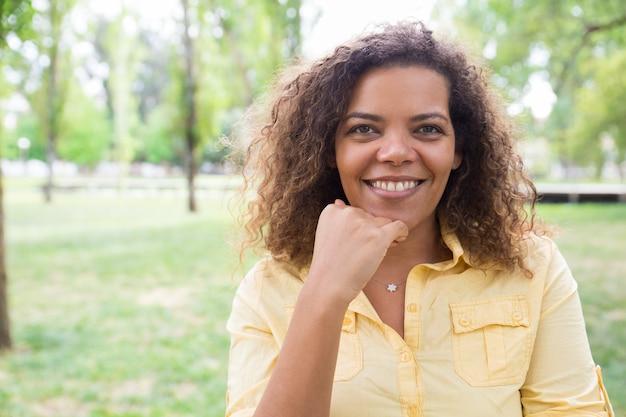 Mulher feliz tocando o queixo e posando para a câmera no parque da cidade