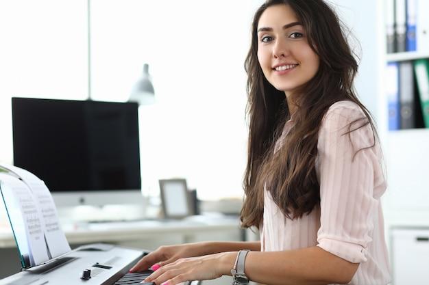 Mulher feliz tocando sintetizador no escritório