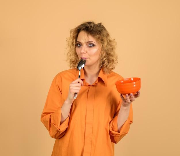 Mulher feliz tomando café da manhã mulher sensual segurando tigela e colher comendo alimentos saudáveis