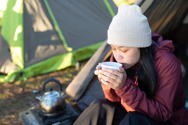 Mulher feliz tomando café em um acampamento pela manhã