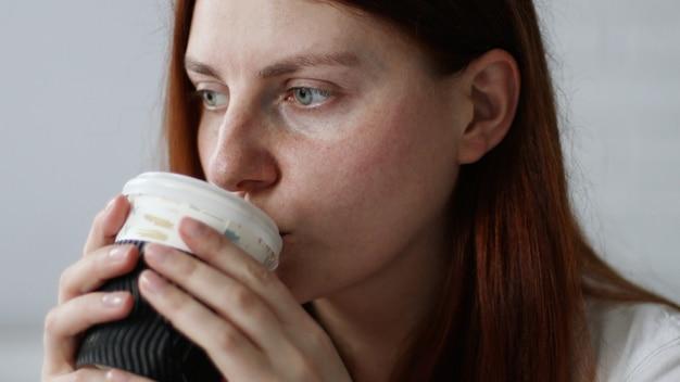 Mulher feliz tomando café em um copo de papel de manhã, sentada no sofá em casa