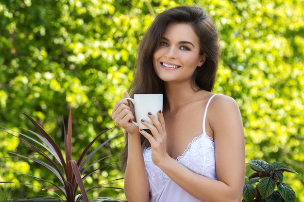 Mulher feliz tomando café na varanda ou no jardim