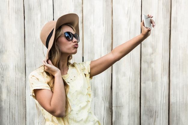 Mulher feliz tomando uma selfie com a câmera