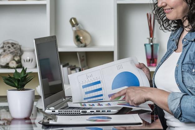 Mulher feliz trabalhando com relatórios enquanto está sentado na mesa com o laptop em casa