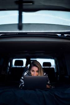 Mulher feliz trabalhando em um laptop enquanto estava deitada na cama em uma van de camping