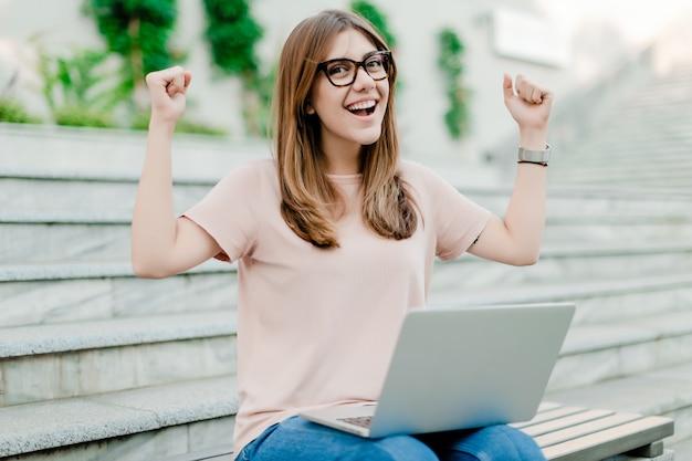 Mulher feliz trabalhando no laptop ao ar livre