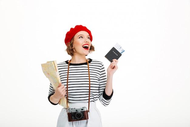 Mulher feliz turista com câmera segurando o mapa e passaporte