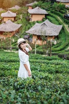 Mulher feliz turista em um vestido branco desfrutar de um belo jardim de chá.