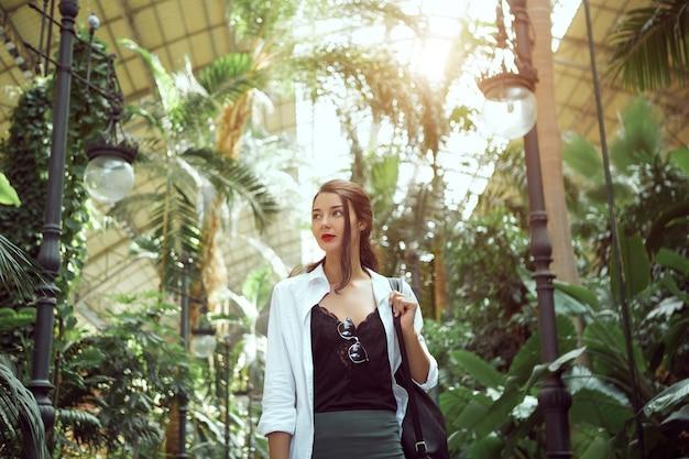 Mulher feliz turista na moda com uma mochila em pé e olhando para longe no trem puerta de atocha