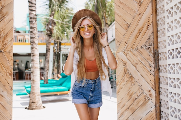 Mulher feliz usa camiseta regata e shorts jeans relaxando no resort nas férias. foto ao ar livre de feliz senhora de cabelos louros com chapéu e óculos de sol se passando perto de espreguiçadeiras.