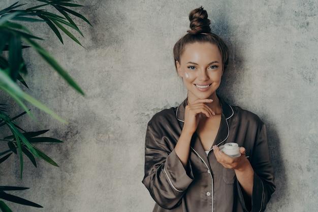 Mulher feliz usa pijama marrom de seda com cabelo preso em um coque alto, posando com creme hidratante na mão durante o procedimento de rotina de beleza matinal, tocando a pele macia e sorrindo para a câmera