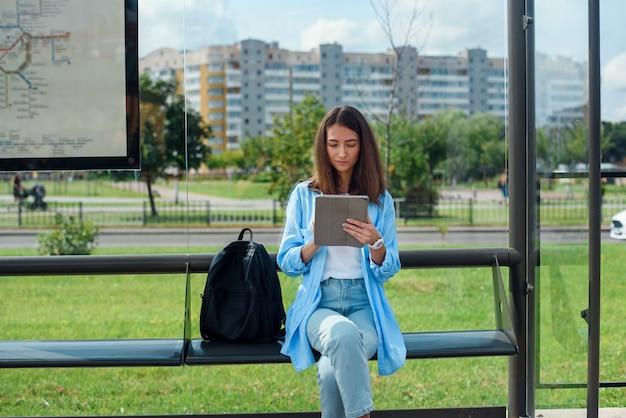 Mulher feliz usa um tablet ou ebook em uma estação de bonde enquanto aguarda o transporte público.