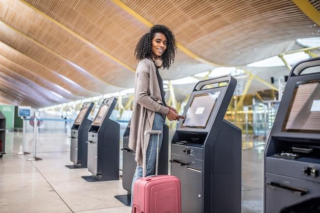 Mulher feliz usando a máquina de check-in no aeroporto, recebendo o cartão de embarque.