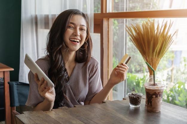 Mulher feliz usando cartão de crédito para compras on-line com tablet no café