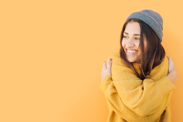 Mulher feliz usando chapéu de malha abraçando-se contra um fundo amarelo