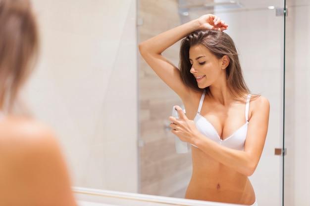 Mulher feliz usando desodorante na axila