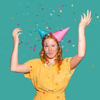 Mulher feliz usando dois cones de aniversário